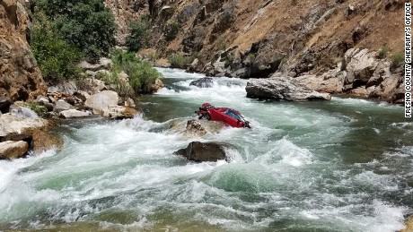 Police are working to retrieve a car trapped in the middle of a raging river in Fresno, California.