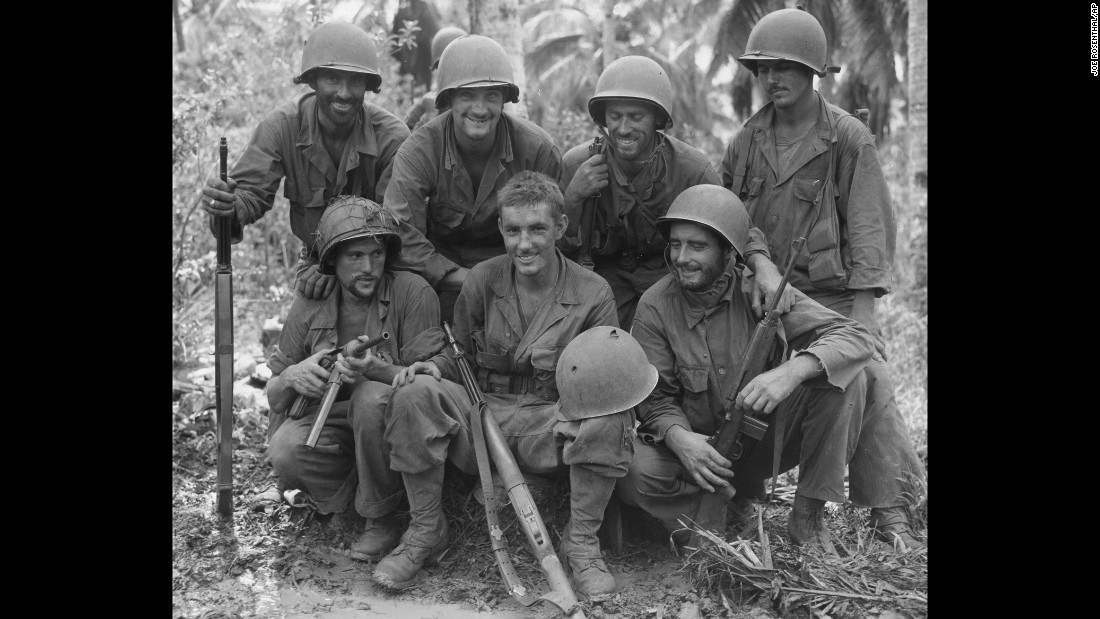 Pvt. William N. Wade, front and center, displays his helmet, punctured by a Japanese sniper near Barrigada, Guam, to his buddies, members of the Army's 77th Infantry Division, Aug. 23, 1944. From left, front row: Cpl. Harold Boyes of Ohio; Pvt. Wade; Pfc. William Kusch, Bayside, New York. Second row: Cpl. Joseph A. Hargraves of Massachusetts; Pfc. Willard Haus of Endicott, New York; Staff Sgt. Stephen Kelly of Brooklyn, New York; and Pvt. Joe Tremallo of Morristown, New Jersey.