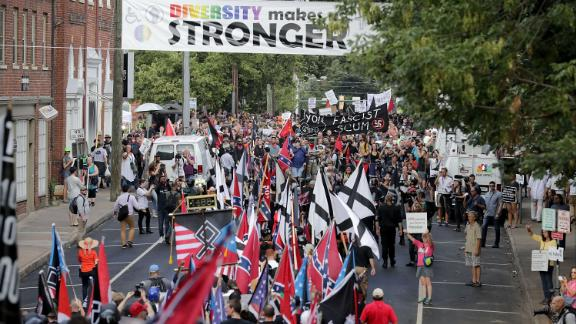 """Hundreds of white nationalists, neo-Nazis and members of the """"alt-right"""" march down East Market Street toward Lee Park during the """"United the Right"""" rally August 12 in Charlottesville, Virginia. After clashes with anti-facist protesters and police the rally was declared an unlawful gathering and people were forced out of Lee Park, where a statue of Confederate General Robert E. Lee is slated to be removed."""