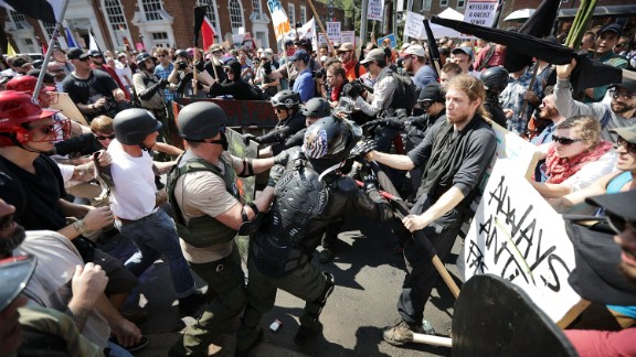 """White nationalists, neo-Nazis and members of the """"alt-right"""" clash with counter-protesters as they enter Lee Park during the """"Unite the Right"""" rally August 12, 2017 in Charlottesville, Virginia. After clashes with anti-fascist protesters and police the rally was declared an unlawful gathering and people were forced out of Lee Park, where a statue of Confederate General Robert E. Lee is slated to be removed."""