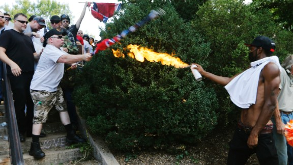 A counter demonstrator uses a lighted spray can against a white nationalist demonstrator at the entrance to Lee Park in Charlottesville, Virginia, Saturday, August 12, 2017. Gov. Terry McAuliffe declared a state of emergency and police dressed in riot gear ordered people to disperse after chaotic violent clashes between white nationalists and counter protestors.