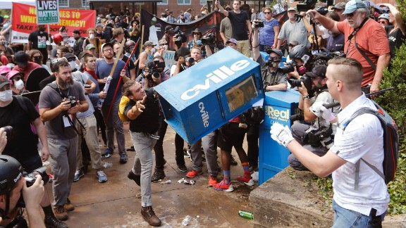 A counterprotester throws a newspaper box at a right-wing rally member at the entrance to Emancipation Park.