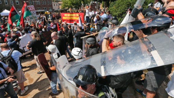 White nationalist demonstrators use shields as they clash with counter demonstrators at the entrance to Lee Park in Charlottesville, Virginia, Saturday, August 12, 2017.   Hundreds of people chanted, threw punches, hurled water bottles and unleashed chemical sprays on each other Saturday after violence erupted at a white nationalist rally in Virginia. At least one person was arrested.