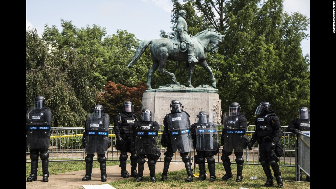 Riot police form a line of defense in front of the statue of Confederate Gen. Robert E. Lee in Emancipation Park, recently renamed from Lee Park.