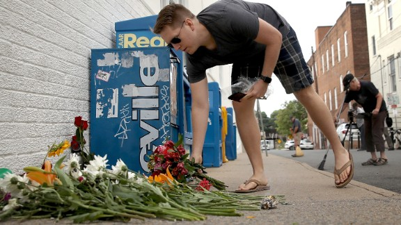 A man places flowers at a makeshift memorial for the victims of yesterday's attack where a car plowed into a crowd of demonstrators opposing a nearby white nationalist rally August 13, 2017 in Charlottesville, Virginia. The city of Charlottesville is still reeling from events following the shutdown of the 'Unite the Right' rally by police after white nationalists, neo-Nallzis and members of the 'alt-right' and counter-protesters clashed near Lee Park.