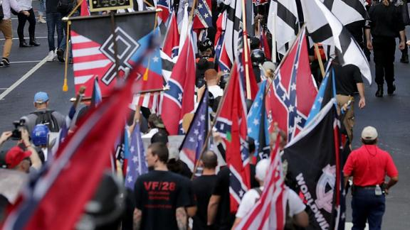 """CHARLOTTESVILLE, VA - AUGUST 12:  Hundreds of white nationalists, neo-Nazis and members of the """"alt-right"""" march down East Market Street toward Emancipation Park during the """"Unite the Right"""" rally August 12, 2017 in Charlottesville, Virginia. After clashes with anti-fascist protesters and police the rally was declared an unlawful gathering and people were forced out of Emancipation Park, where a statue of Confederate General Robert E. Lee is slated to be removed.  (Photo by Chip Somodevilla/Getty Images)"""
