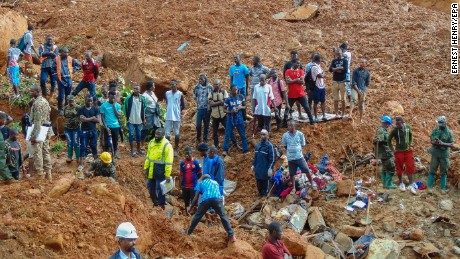 Residents and rescuers survey the damage from the mudslide in Regent.
