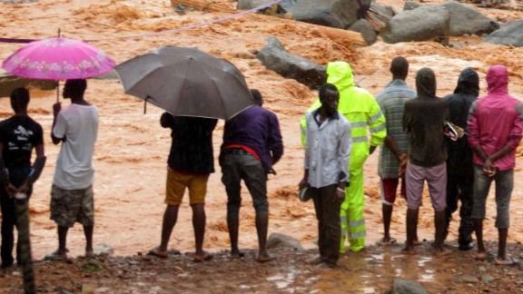 Bystanders look on as floodwaters rage past a damaged building in an area of Freetown on August 14, 2017, after landslides struck the capital of the west African state of Sierra Leone.               At least 312 people were killed and more than 2,000 left homeless when heavy flooding hit Sierra Leone's capital of Freetown, leaving morgues overflowing and residents desperately searching for loved ones. An AFP journalist at the scene saw bodies being carried away and houses submerged in two areas of the city, where roads turned into churning rivers of mud and corpses were washed up on the streets. / AFP PHOTO / SAIDU BAH        (Photo credit should read SAIDU BAH/AFP/Getty Images)