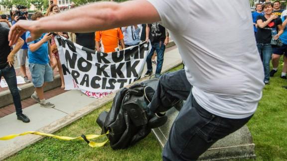Protesters kick the fallen statue of a Confederate soldier in Durham, North Carolina.