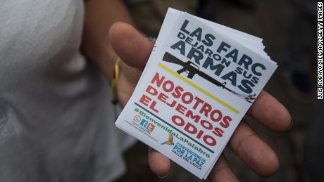 "A woman holds stickers reading ""The FARC left their weapons, let us leave the hatred"" during an event by the civil society in Cali, Valle del Cauca departament, Colombia, on June 27, 2017, in support of the complete disarmament of the FARC and the end of Latin America's oldest armed guerrilla force. / AFP PHOTO / LUIS ROBAYO        (Photo credit should read LUIS ROBAYO/AFP/Getty Images)"