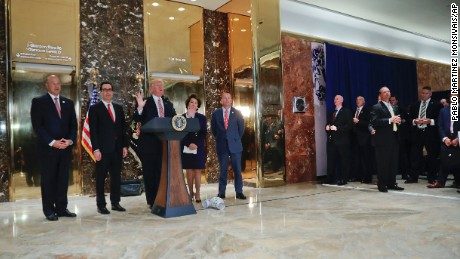 President Donald Trump speaks to the media in the lobby of Trump Tower. With Trump are from left, National Economic Council Director Gary Cohn, Treasury Secretary Steven Mnuchin, Transportation Secretary Elaine Chao and OMB Director Mick Mulvaney.