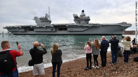 People line the shore to watch as tug boats maneuver the 65,000-ton British aircraft carrier HMS Queen Elizabeth into Portsmouth Harbour.