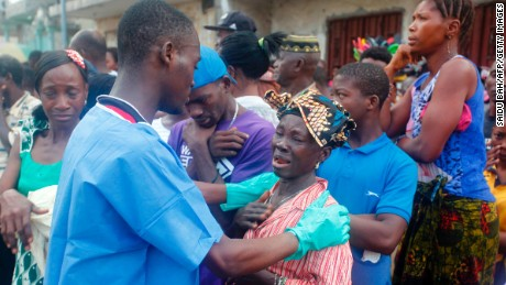 A relative of a mudslide victim receives comfort Wednesday at the Freetown morgue.