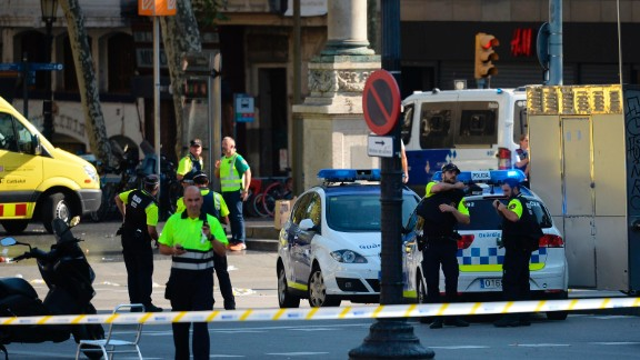 """Medical staff members and policemen stand in a cordoned off area after a van ploughed into the crowd, injuring several persons on the Rambla in Barcelona on August 17, 2017. Police in Barcelona said they were dealing with a """"terrorist attack"""" after a vehicle ploughed into a crowd of pedestrians on the city"""