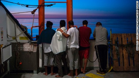 Migrants watch sunrise from the Aquarius rescue ship after their transfer from the NGO Migrant Offshore Aid Station (MOAS) in August 2017.