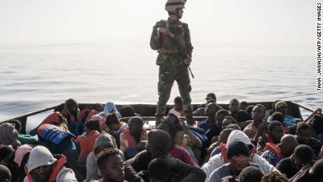 A Libyan coast guardsman stands on a boat during the rescue of 147 migrants off the coastal town of Zawiyah, west of Tripoli, in June.