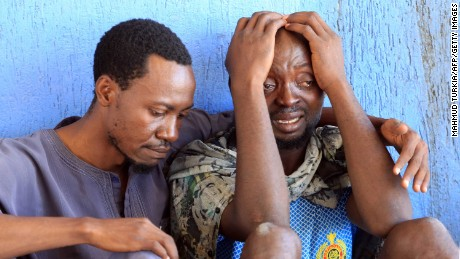 Migrants react after being returned to a detention center in Libya.