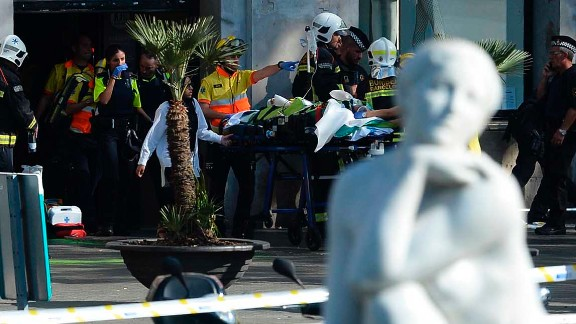 """A person is stretched out of a mall by medical staff members in a cordoned off area after a van ploughed into the crowd, injuring several persons on the Rambla in Barcelona on August 17, 2017.Police in Barcelona said they were dealing with a """"terrorist attack"""" after a vehicle ploughed into a crowd of pedestrians on the city's famous Las Ramblas boulevard on August 17, 2017. Police were clearing the area after the incident, which has left a number of people injured. / AFP PHOTO / Josep LAGO        (Photo credit should read JOSEP LAGO/AFP/Getty Images)"""