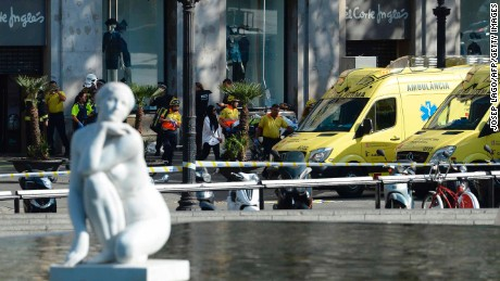 A person is stretched out of a mall by medical staff members in a cordoned off area after a van ploughed into the crowd, injuring several persons on the Rambla in Barcelona on August 17, 2017.