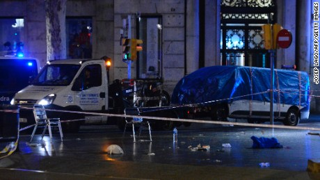 "The van who ploughed into the crowd, killing at least 13 people and injuring around 100 others is towed away from the Rambla in Barcelona on August 18, 2017. A driver deliberately rammed a van into a crowd on Barcelona's most popular street on August 17, 2017 killing at least 13 people before fleeing to a nearby bar, police said.  Officers in Spain's second-largest city said the ramming on Las Ramblas was a ""terrorist attack"". The driver of a van that mowed into a packed street in Barcelona is still on the run, Spanish police said. / AFP PHOTO / Josep LAGO        (Photo credit should read JOSEP LAGO/AFP/Getty Images)"