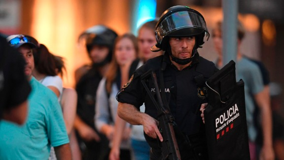 Spanish policemen stand guard in a cordoned off area after a van ploughed into the crowd, killing 13 persons and injuring over 50 on the Rambla in Barcelona on August 17, 2017. A driver deliberately rammed a van into a crowd on Barcelona
