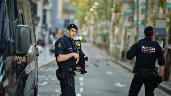 Armed police officers patrol a deserted street in Las Ramblas, in Barcelona, Spain, Friday, Aug. 18, 2017. A white van jumped up onto a sidewalk and sped down a pedestrian zone Thursday in Barcelona