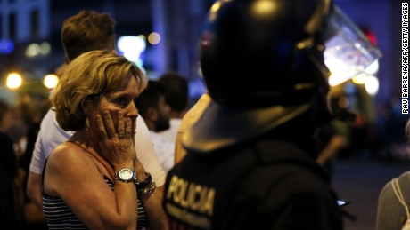 A woman gestures as she is escorted out by Spanish policemen outside a cordoned off area after a van ploughed into the crowd, killing 13 persons and injuring over 80 on the Rambla in Barcelona on August 17, 2017.