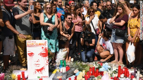 People stand next to flowers, candles, a poster reading 'Pray for Barcelona' and other items set up on the Las Ramblas boulevard in Barcelona as they pay tribute to the victims of the Barcelona attack, a day after a van ploughed into the crowd, killing 13 persons and injuring over 100 on August 18, 2017.