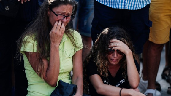 Two women cry at the street memorial in Barcelona on Friday, August 18.