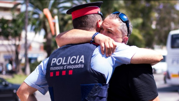 A man embraces a police officer in Cambrils on August 18. Earlier in the day, officers had engaged in a shootout with five attackers who drove a car into several pedestrians. All five were shot dead by police, four of them by one officer, police said.