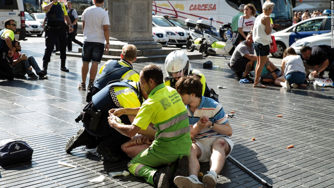 Medics and police tend to injured people near the scene of the attack in Barcelona.