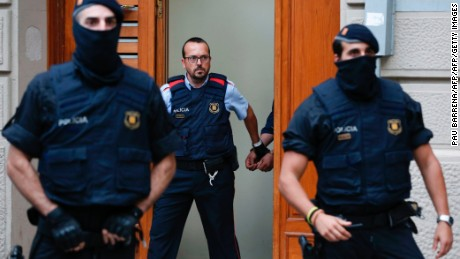 Catalan autonomous police officers, known as Mosso d'Esquadra, detain a cuffed suspect in Ripoll during a search linked to the deadly terror attacks in Barcelona and the seaside resort of Cambrils on August 18, 2017, a day after a van ploughed into the crowd, killing 14 persons and injuring over 100 on the Rambla in Barcelona.  Drivers have ploughed on August 17, 2017 into pedestrians in two quick-succession, separate attacks in Barcelona and another popular Spanish seaside city, leaving 14 people dead and injuring more than 100 others. In the first incident, which was claimed by the Islamic State group, a white van sped into a street packed full of tourists in central Barcelona on Thursday afternoon, knocking people out of the way and killing 13 in a scene of chaos and horror. Some eight hours later in Cambrils, a city 120 kilometres south of Barcelona, an Audi A3 car rammed into pedestrians, injuring six civilians -- one of them critical -- and a police officer, authorities said.  / AFP PHOTO / PAU BARRENA        (Photo credit should read PAU BARRENA/AFP/Getty Images)