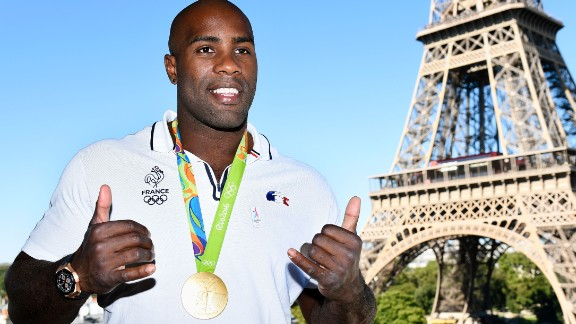 French judoka Teddy Riner poses with his gold medal in front of the Eiffel tower on August 23, 2016 in Paris.  France's Olympic team landed in Paris on August 23, 2016 after winning 42 medals in Rio, including 10 golds, a postwar record for the overall medal count. / AFP / Bertrand GUAY        (Photo credit should read BERTRAND GUAY/AFP/Getty Images)