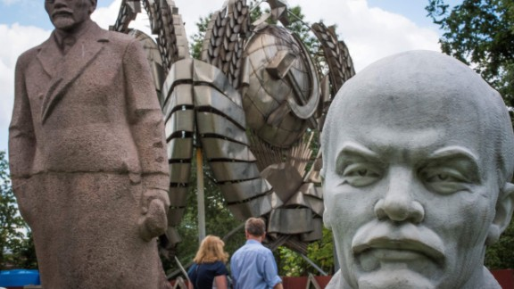 A picture taken on July 11, 2017 shows sculptures of the founder of the Soviet Union Vladimir Lenin next to a state emblem of the USSR at the Muzeon park of Arts in Moscow.