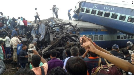 Police and volunteers look for survivors Saturday in the wreckage of a train derailment in northern India.