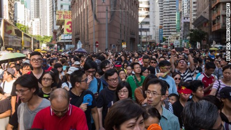 Thousands of protestors march through Wanchai district in support of the three men, who were jailed last week after being convicted of unlawful assembly.