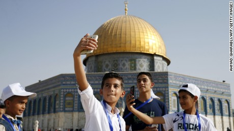 Palestinian children from Gaza pose for a picture near the Dome of the Rock mosque.