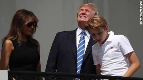President Donald Trump looks up toward the Solar Eclipse while standing with his wife first lady Melania Trump and their son Barron, on the Truman Balcony at the White House on August 21, 2017.