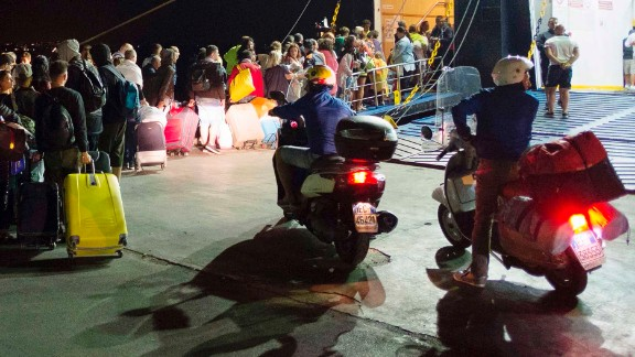 Tourists board a ferry early Tuesday morning in Ischia  after an earthquake hit the popular Italian tourist island.