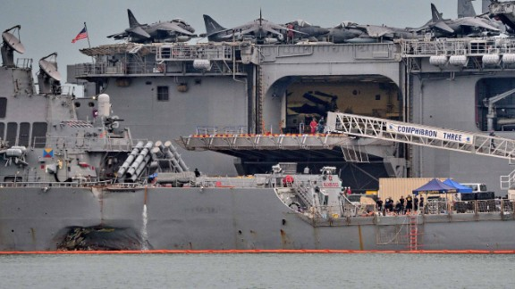The guided-missile destroyer USS John S. McCain (foreground), seen with a hole on its portside after a collision with a tanker, docks next to the USS America (behind) at Changi naval base in Singapore on August 22, 2017.