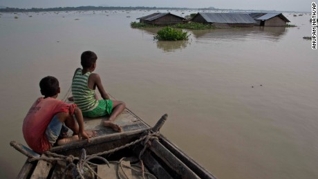Flood-affected villagers travel by boat in floodwaters in the Morigaon district in the northeastern Indian state of Assam on August 15.