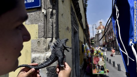 "A fan holds a Godzilla plastic toy while watching the shooting of scenes of the movie ""Godzilla, King of the Monsters"" in the historical centre of Mexico City on August 20, 2017. Godzilla invades Mexico City as scenes from the Japanese monster's latest movie directed by Michael Dougherty are filmed in the capital. / AFP PHOTO / Yuri CORTEZ        (Photo credit should read YURI CORTEZ/AFP/Getty Images)"
