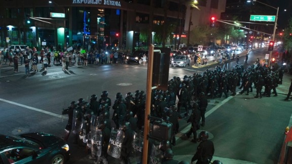 Riot police form a line outside the convention center.