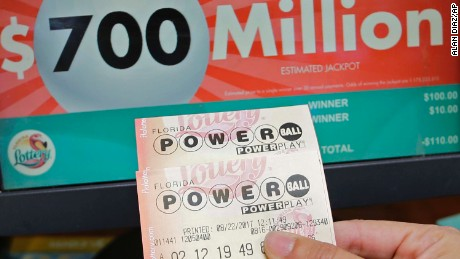A customer shows her purchased Powerball tickets for Wednesday's drawing, Tuesday, Aug. 22, 2017, in Hialeah, Fla. The winner could take the $700 million annuity option (paid out over 29 years) or the $443.3 million cash prize, minus state and federal taxes. (AP Photo/Alan Diaz)