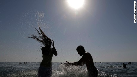 A Lebanese couple enjoy themselves in the water at the beach of the southern port city of Tyre, Lebanon, Sunday, Sept. 20, 2015. (AP Photo/Hassan Ammar)