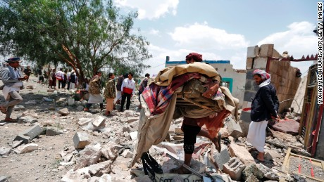A Yemeni man carries his belongings after an airstrike heavily damaged his neighborhood.