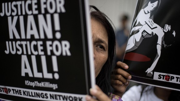 An activist holds a poster against extra-judicial killings during a protest in Manila on August 23, 2017.  The alleged murder by local police of 17-year-old Kian Delos Santos last week triggered rare protests against Philippines