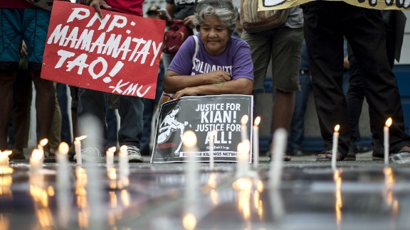 An activist holds a poster against extra-judicial killings during a protest in Manila on August 23, 2017.