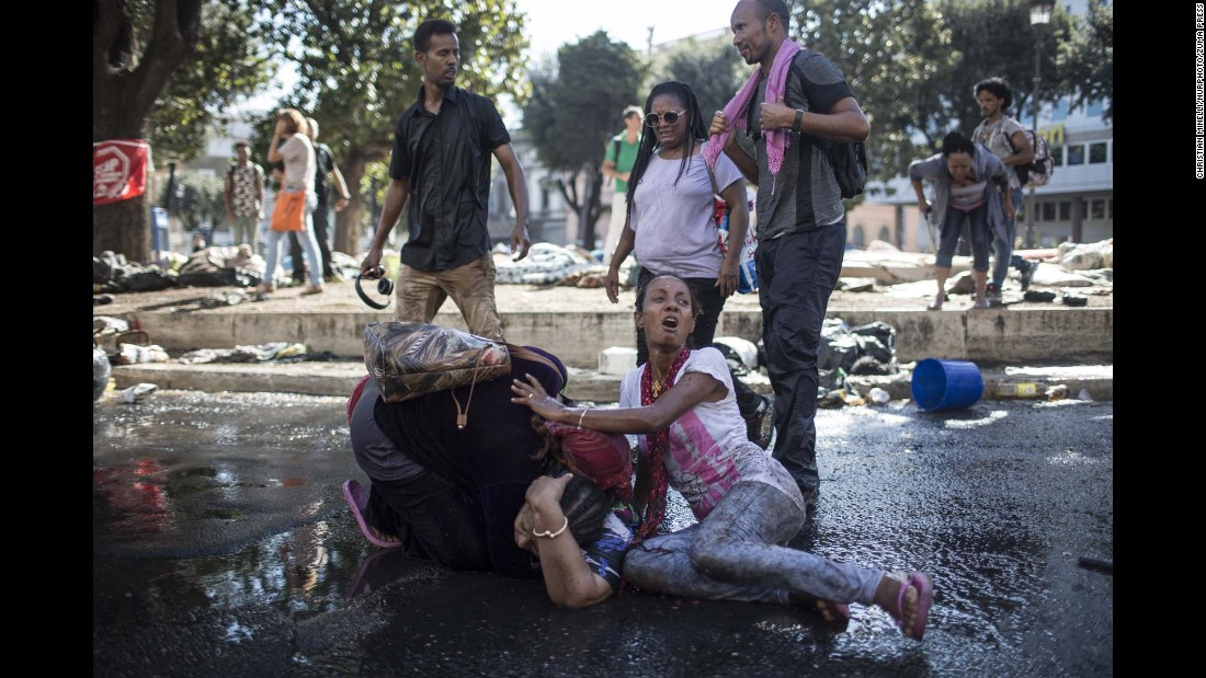 "An injured woman receives assistance after police used water cannons to disperse migrants who were occupying a city square in Rome on Thursday, August 24. The migrants had been evicted from a building they had been squatting in for years, <a href=""http://www.latimes.com/world/europe/la-fg-italy-refugees-crackdown-20170824-story.html"" target=""_blank"">according to the Los Angeles Times.</a>"