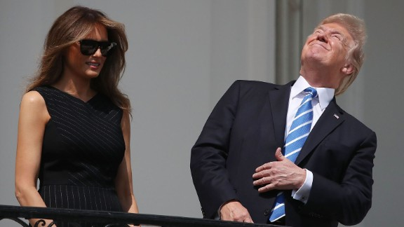President Donald Trump looks up toward the Solar Eclipse while joined by his wife first lady Melania Trump on the Truman Balcony at the White House on August 21, 2017.